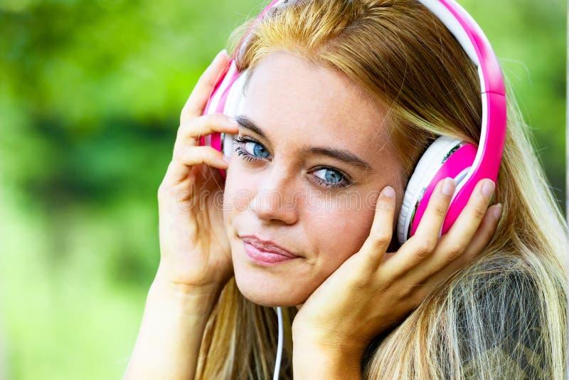 有耳机的美丽的年轻白肤金发的妇女 库存图片