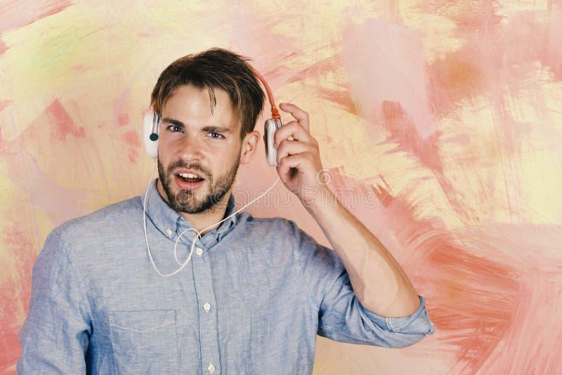 有耳机的美国英俊的有胡子的人 快乐的少年dj听的歌曲通过耳机 音乐生活方式 免版税图库摄影