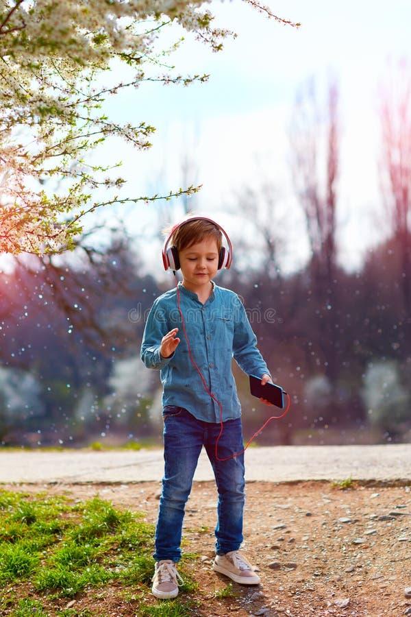 有耳机的逗人喜爱的孩子男孩听音乐和跳舞在开花的公园 库存图片