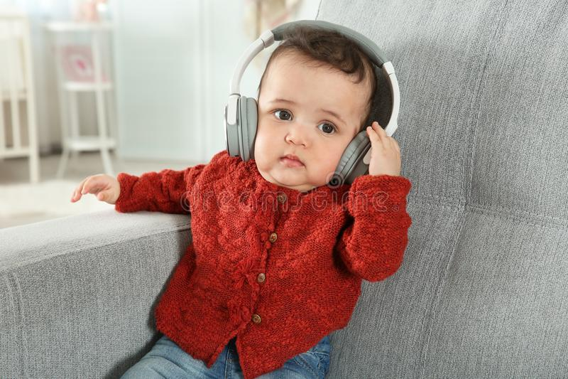 有耳机的逗人喜爱的矮小的婴孩听到音乐的 库存图片
