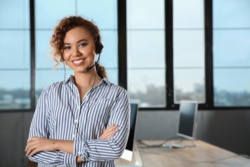 有耳机的非裔美国人的技术支持操作员在办公室 免版税库存图片