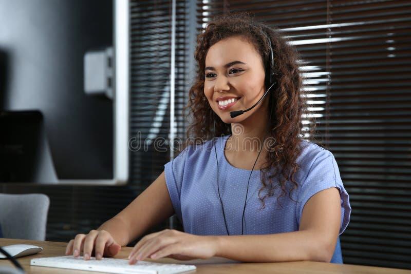 有耳机的非裔美国人的技术支持操作员 库存照片