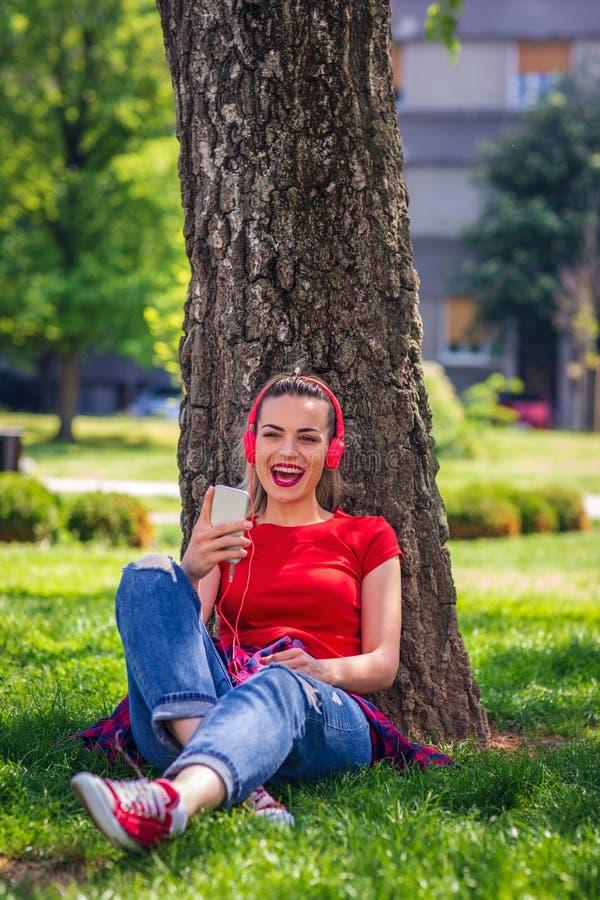 有耳机的音乐激情凉快的妇女听到音乐的  免版税库存照片