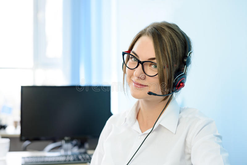 有耳机的年轻可爱的微笑的用户支持电话操作员在办公室 免版税图库摄影