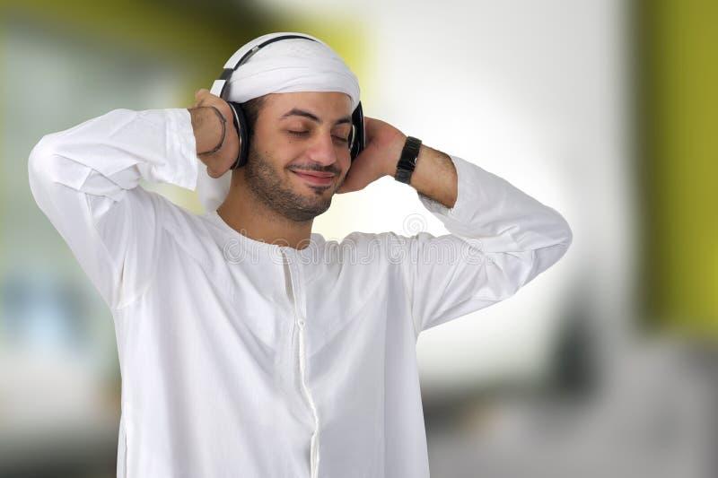 有耳机的年轻愉快的阿拉伯人听到音乐的 免版税库存照片