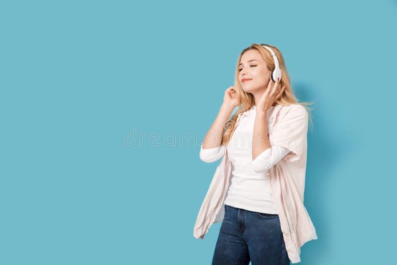 有耳机的年轻美丽的女孩 库存照片