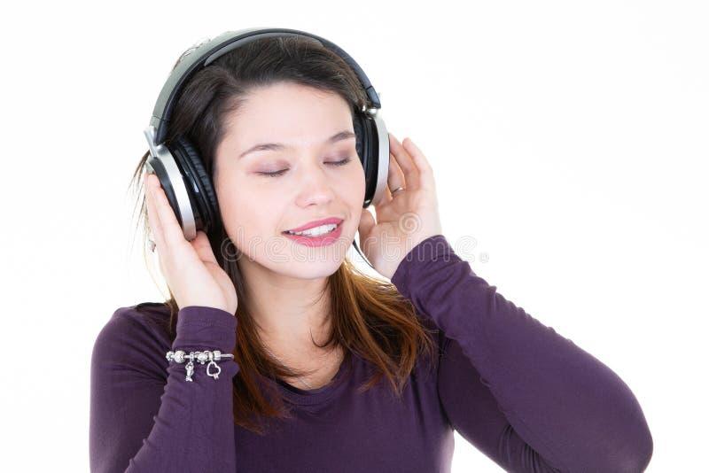 有耳机眼睛的年轻深色的妇女关闭了 免版税库存图片