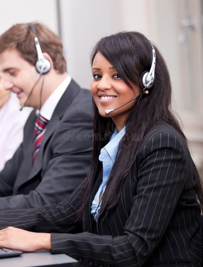有耳机callcenter的非洲女商人 库存图片