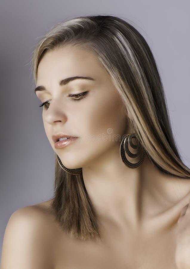 有耳环的美丽的白肤金发的妇女 免版税图库摄影
