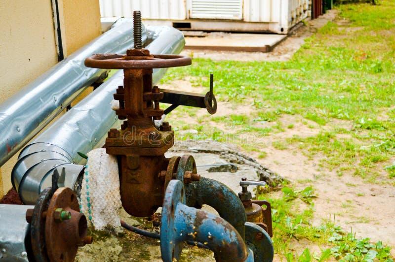 有耳轮缘阀门转折的铁老生锈的防腐蚀工业金属油和煤气的管子和分支 图库摄影
