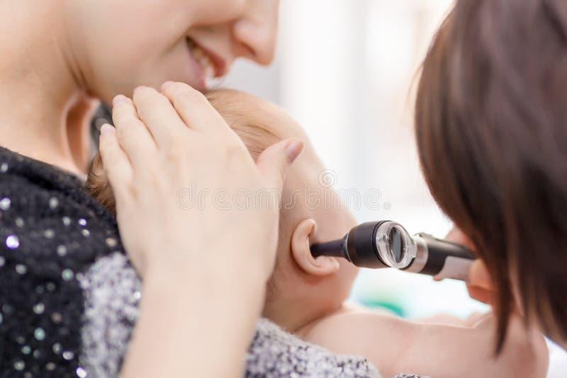 有耳镜的医生审查的childs耳朵 抱着婴孩用手的妈妈 儿童医疗保健和疾病预防 免版税库存照片
