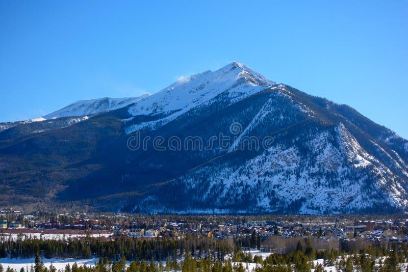 有耸立在与雪的背景中的一座大山的冬天镇 库存图片