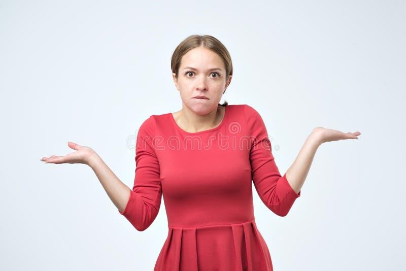 有耸肩的缺乏信心的妇女和实施打手势不确定性 免版税库存照片