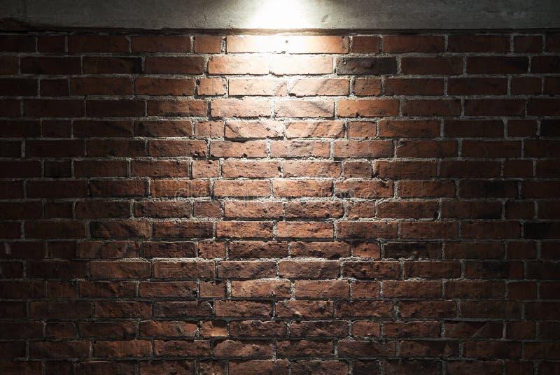有聚光灯的,纹理脏的深红砖墙 免版税图库摄影