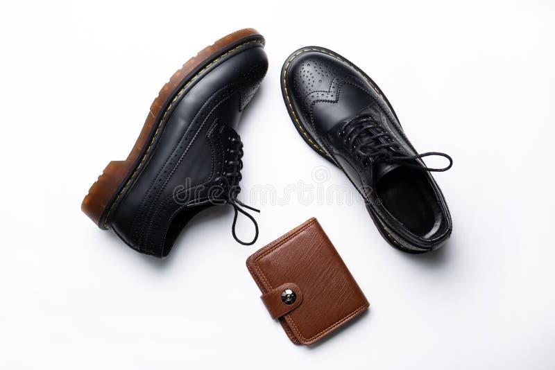 有聚氨酯鞋底的黑皮革德比鞋子和有一个按钮的一个棕色钱包在白色背景 图库摄影