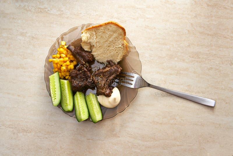 有肉肋骨、菜和调味汁的板材 免版税库存图片