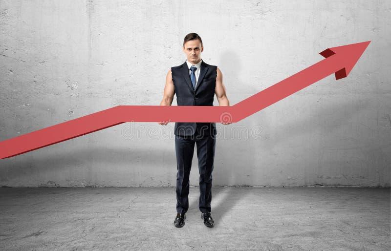 有肌肉胳膊和拿着与一个向上的箭头的商人大红线图表 免版税库存照片
