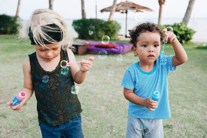 有肥皂泡的小男孩在热带庭院里 免版税库存图片