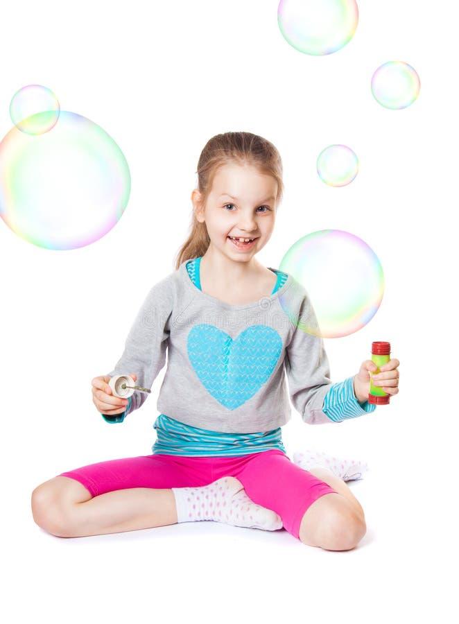 有肥皂泡的愉快的小女孩 库存照片