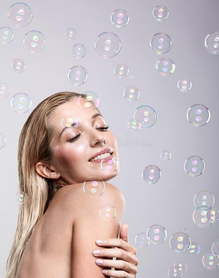 有肥皂泡的美丽的年轻白肤金发的妇女在灰色backgroun 图库摄影