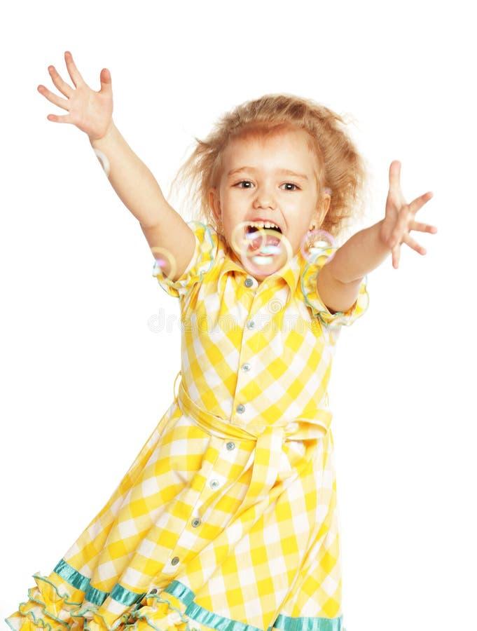 有肥皂泡的滑稽的可爱的小女孩 图库摄影