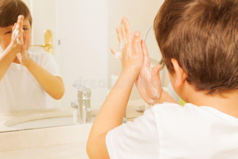 有肥皂的男孩洗涤的手和看在镜子 免版税库存照片