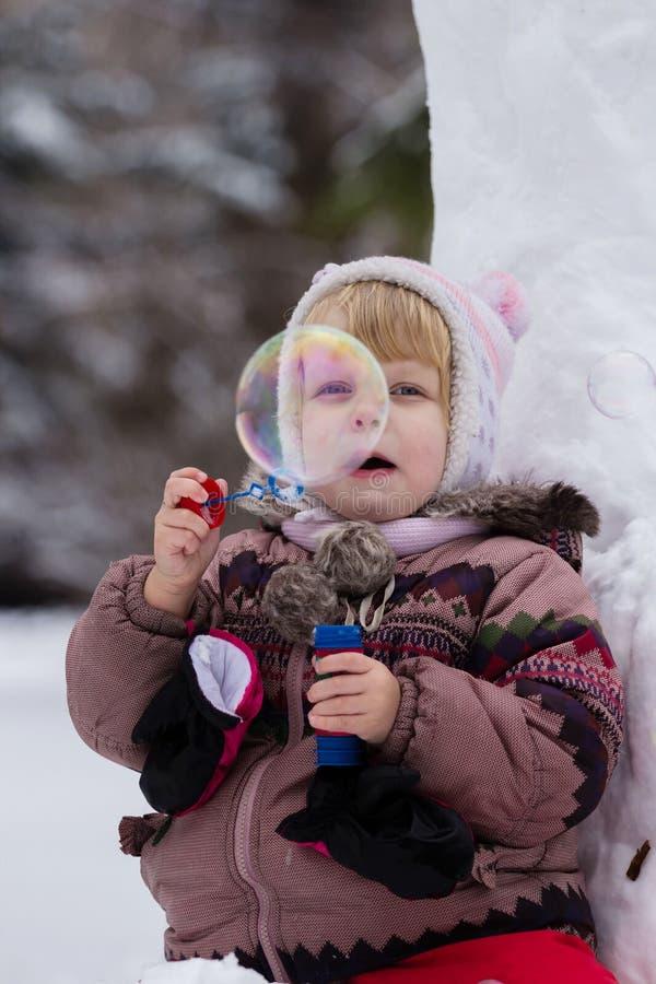有肥皂bubles的小女孩在冬天 免版税库存图片