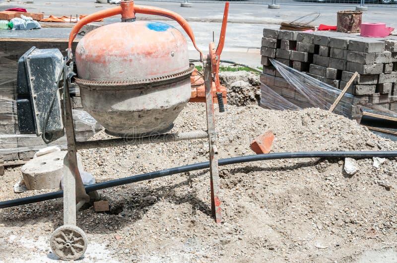 有肮脏的膏药搅拌器的,堆小建筑工作站点沙子,堆步行者边路的路面瓦片在城市 图库摄影