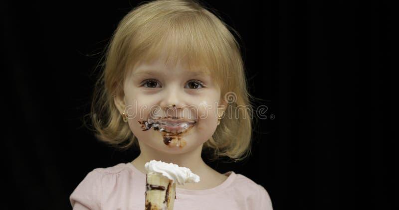 有肮脏的面孔的孩子吃香蕉用熔化巧克力和打好的奶油 免版税库存图片