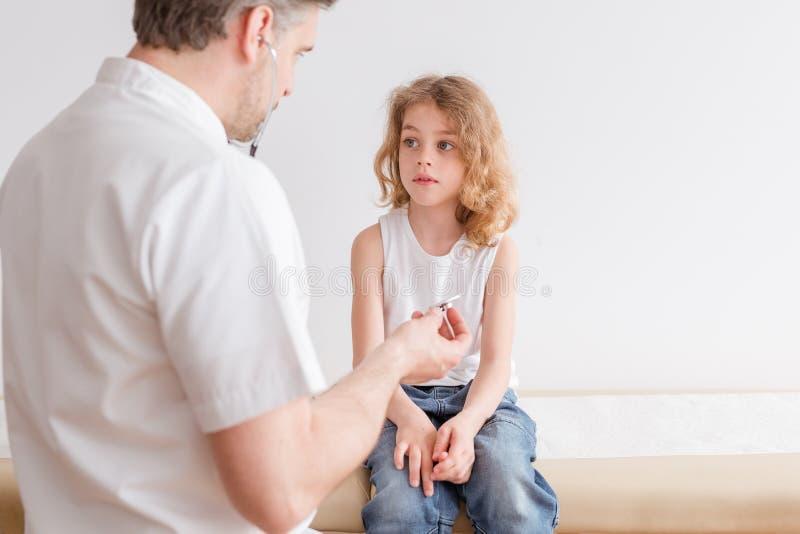 有肺炎症状的不适的孩子和专业医生在医院 免版税库存照片