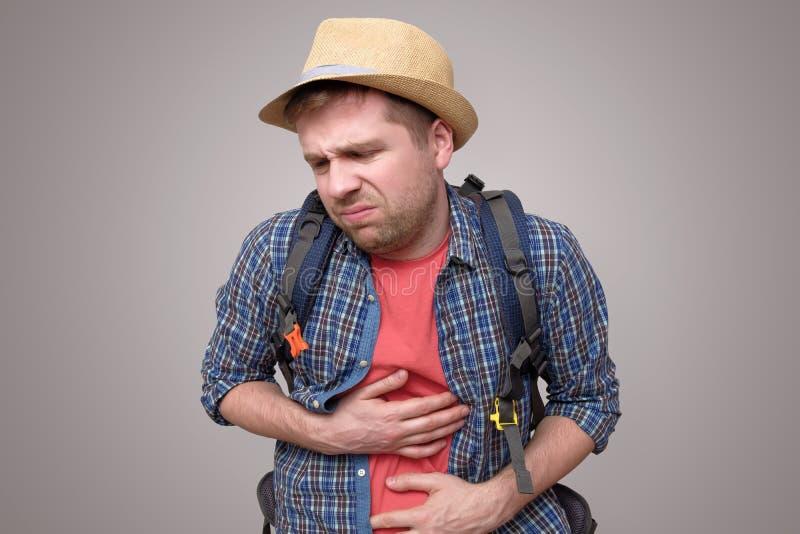 有胃痛消化不良的年轻旅游人 库存图片
