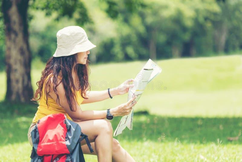 有背包冒险发现方向和坐的藏品地图的亚裔妇女徒步旅行者或旅客在密林森林outdoo放松 库存照片