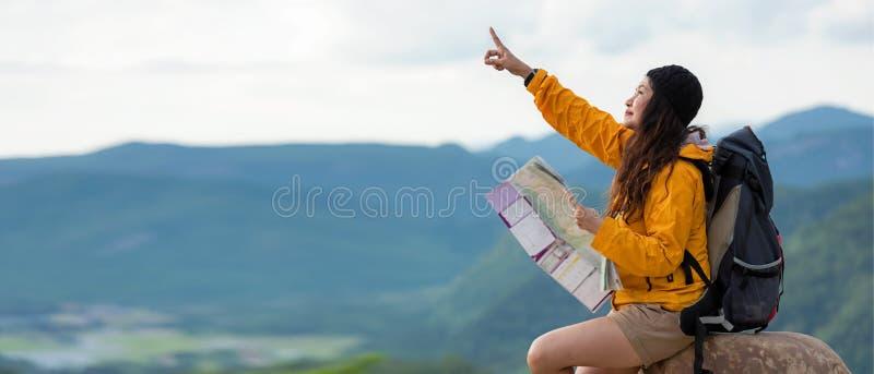 有背包冒险发现方向和坐的藏品地图的妇女徒步旅行者或旅客在山自然,文本放松为 库存照片