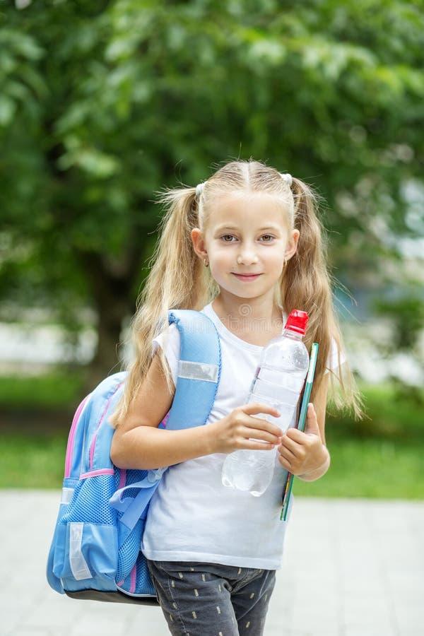 有背包和一个瓶的一个孩子水 学校的概念,研究,教育,友谊,童年 免版税库存图片