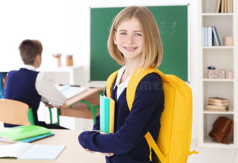 有背包和书站立的逗人喜爱的女孩 免版税图库摄影