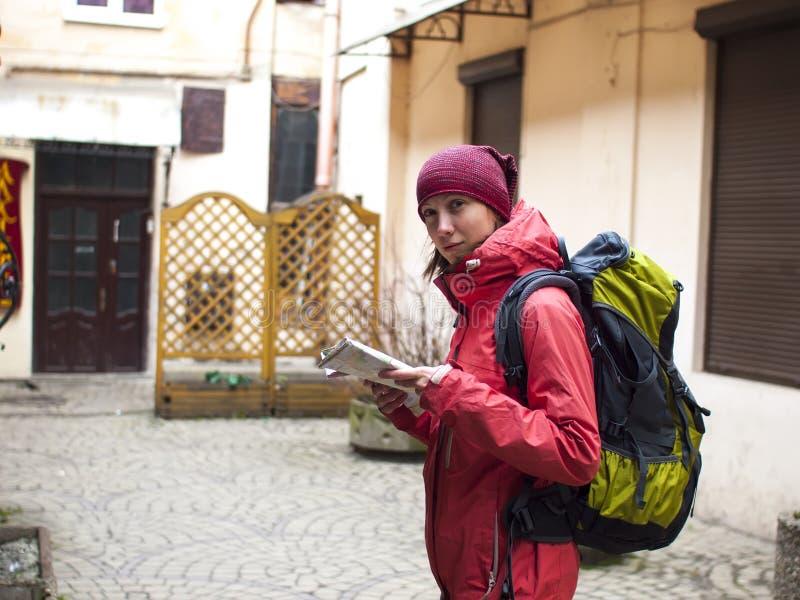 有背包和地图的女孩 库存照片
