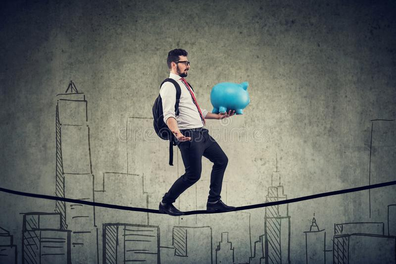 有背包和存钱罐走的平衡的人在城市地平线上的一条绳索 免版税库存图片