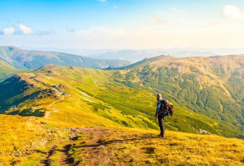 有背包和山全景的旅客 免版税库存照片