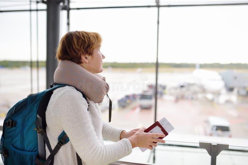 有背包和旅行枕头的妇女在飞机上在窗口里看在机场的等候室 库存照片