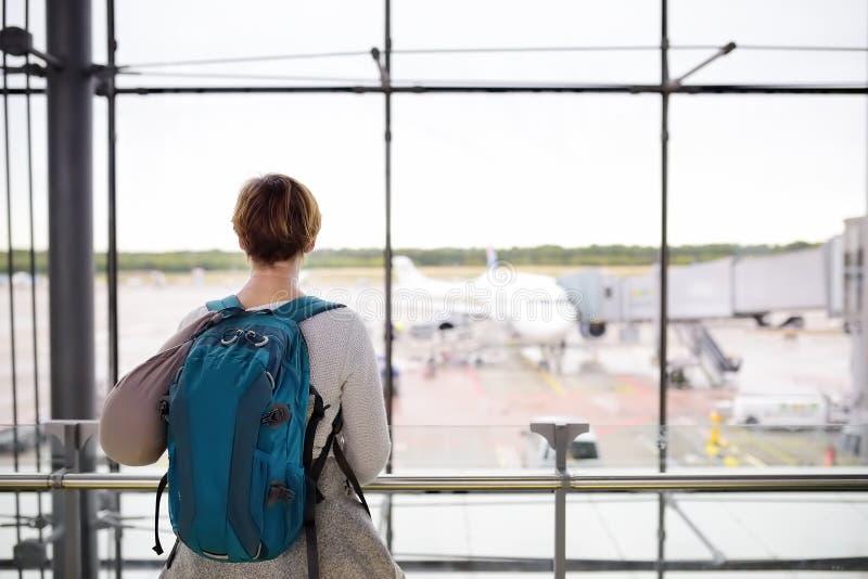 有背包和旅行枕头的妇女在飞机上在窗口里看在机场的等候室 免版税库存图片