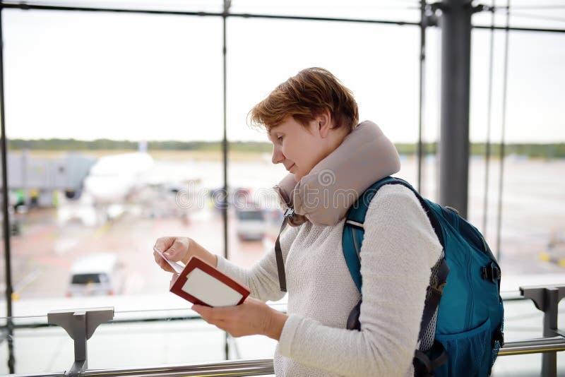 有背包和旅行枕头的成熟妇女检查她的在机场的等候室的票 库存照片