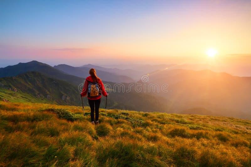 有背包和棍子的红发女孩运动员在绿色小丘站立并且看高山风景 库存图片