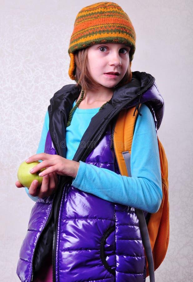 有背包和苹果的愉快的微笑的女小学生 免版税库存照片