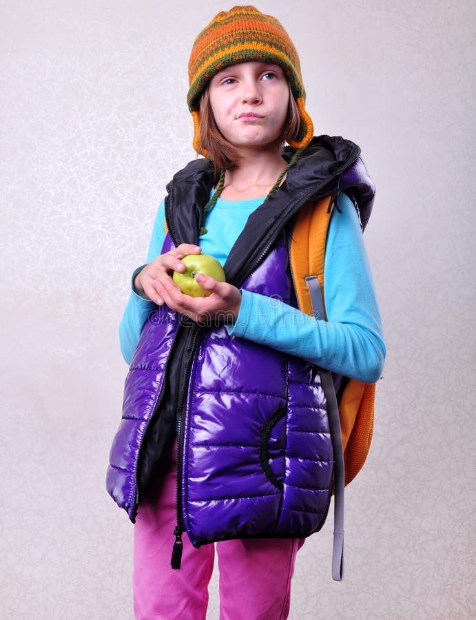 有背包和苹果的Scaptical女小学生 免版税库存照片