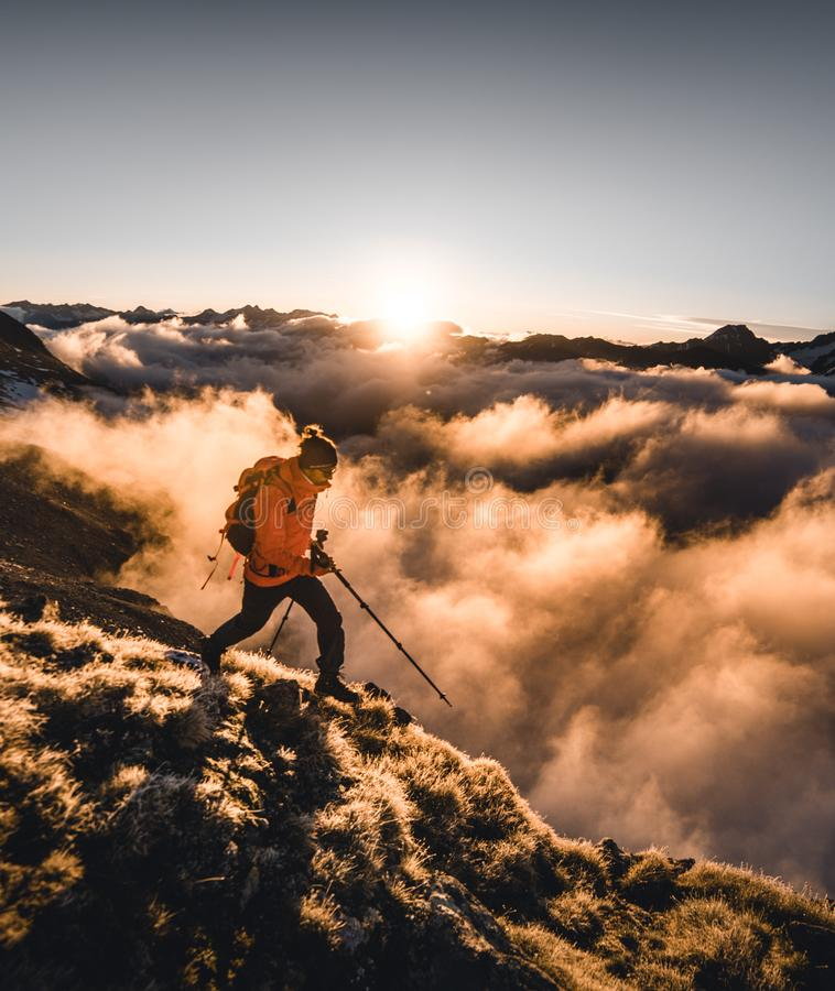 有背包和走的杆的年轻徒步旅行者,站立在看日落的山的峰顶 使谷模糊 免版税图库摄影