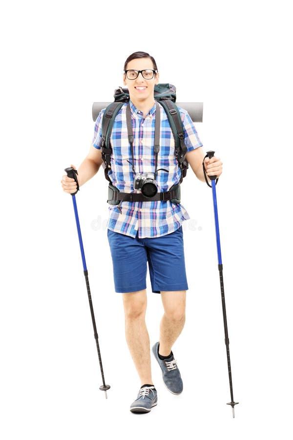 有背包和远足的杆走微笑的远足者 库存照片