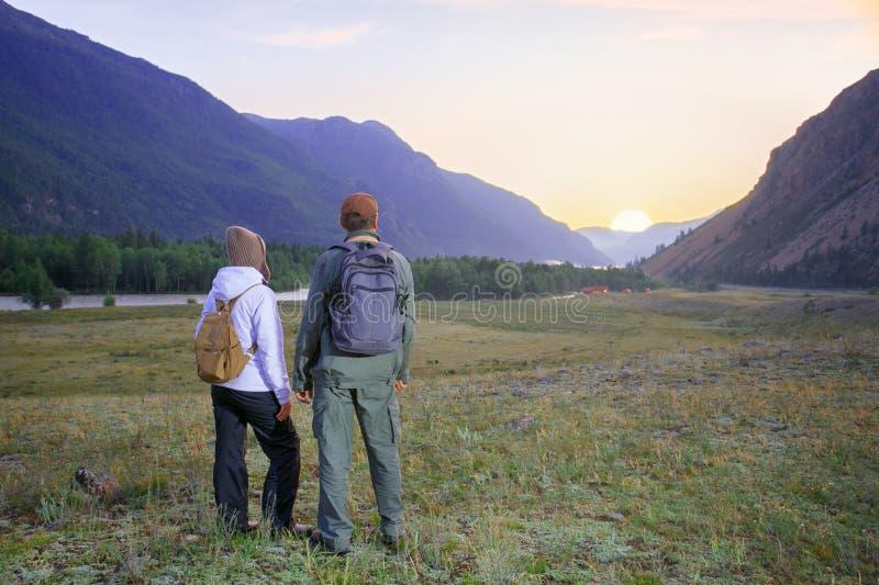 有背包放松的徒步旅行者 愉快的夫妇感觉自由并且享用山的美丽的秋天森林 免版税库存图片