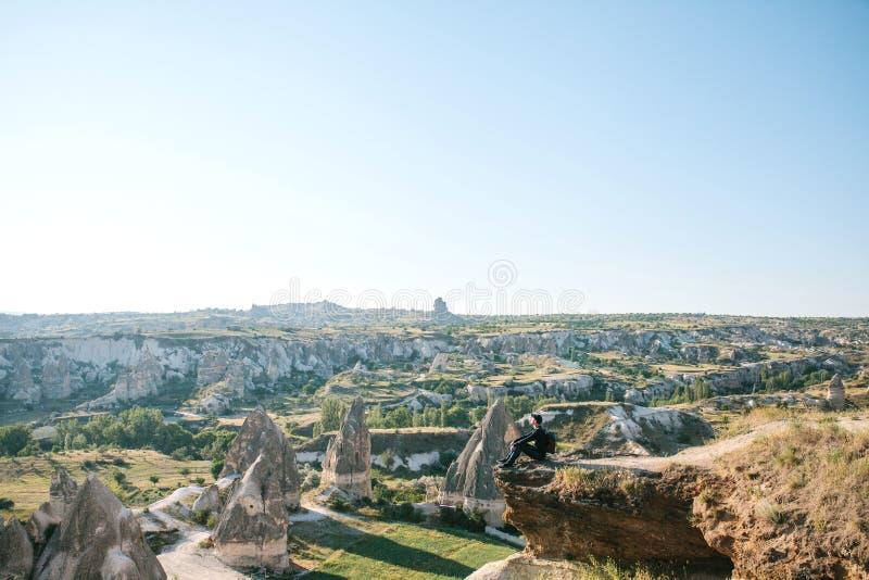 有背包的一个人坐在小山顶部在卡帕多细亚在土耳其 免版税库存照片