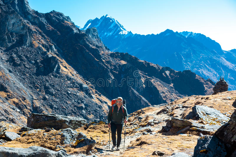 有背包的一个人走在山小径的 库存图片
