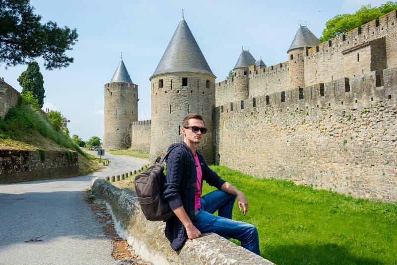 有背包的一个年轻人在medieva的堡垒墙壁附近坐 免版税图库摄影